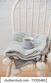 tea mug and knitted textured things on a white wooden chair, the concept of coziness, autumn, knitted things