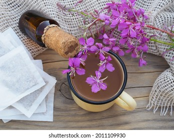 Tea in a mug, tincture, tea bags, chamerion angustifolium with pink flowers on a wooden table. Useful plant epilobium parviflorum for use in herbal alternative medicine, homeopathy and cosmetology