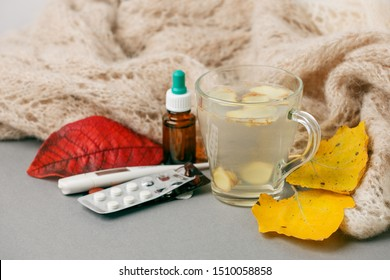 Tea mug with warm scarf, thermometer and nose drops, pills on gray surface with red leaves, autumn fall winter seasonal flu cold remedy background