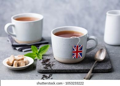 Tea in mugs with British flag tea bag label. Grey background. Close up.