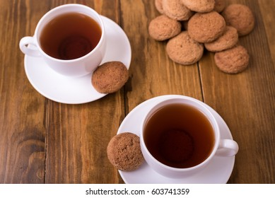 Tea and oaten cookies on a wooden table