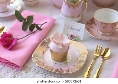 tea party place setting with pink tea cup, cupcake, napkin, pink rose and gold cake fork and gold teaspoon