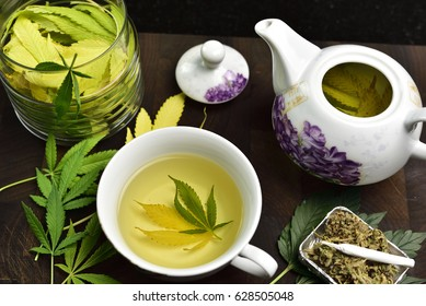 tea pot with cannabis tea in tea cup on wooden butcher cutting board with joint, cannabis bud, glass jar with cannabis leaves and cannabis leaves