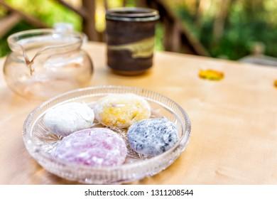 Tea pot and mochi rice cake Japanese dessert wagashi colorful daifuku on table color with four pieces closeup