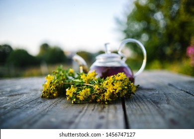 Tea pot with St.-John's wort on wooden table, nature background.
