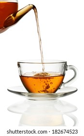 Tea pouring into glass cup isolated in white