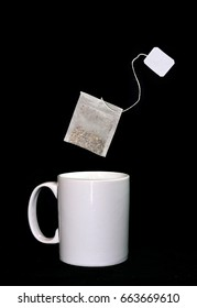 Tea sac flying over a white cup isolated on a black background