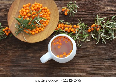 Tea of sea-buckthorn berries with branch on dark wooden background