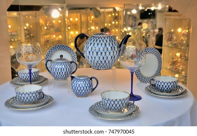 tea set blue white with glasses amid the golden yellow lights