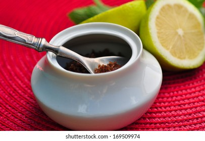 Tea spoon of brown sugar and limes in the background