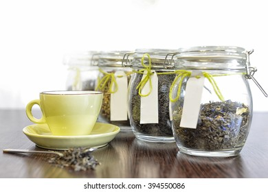 tea in spoon, glass jars and cup on old wooden table with white background