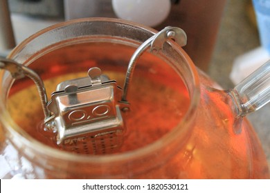 Tea strainer in form of a robot hanging in cup with tea