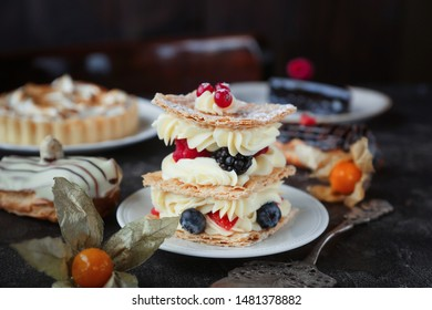 Tea and sweets on a dark background, Mille-feuille, Eclairs, Tart, Decorative with flowers, Selective focus