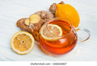 Tea in teapot with ginger roots and lemon slices on white wooden background