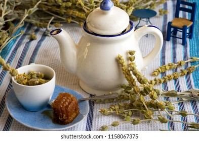 Tea time with a beautiful teapot with Greek mountain tea and a tea cup and honeycomb