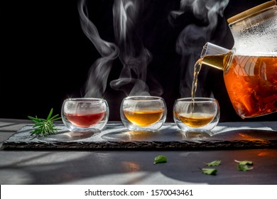 Tea time to brew loose-leaf or flower . dark mood.Hot water is poured from the kettle into a cup with tea leaves.