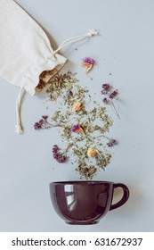 Tea time. Dry herbal tea and cup on the gray background, top view.