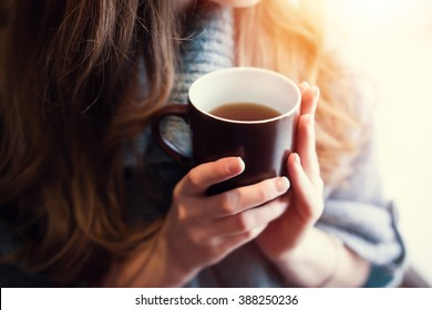 Tea time at morning. Woman hands holding cup of tea in the morning.
