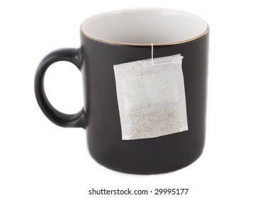 Tea time in office - empty black mug with teabag ready