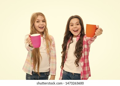 It is tea time. Relaxing with drink. Tea break. Children do not drink enough during school day. Make sure kids drink enough water. Girls kids hold cups. Sisters hold mugs. Drinking tea while break.