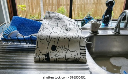Tea towel with cat design and dishcloths on dish rack in kitchen