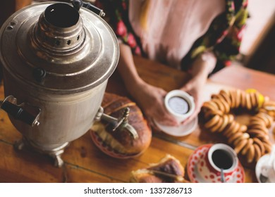 tea, traditional Russian dishes and treats, a samovar on the table, the hands of a woman in a national kerchief are holding a cup of tea, Moskow
