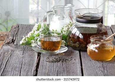 Tea in a transparent cup and a jug with milk on a wooden table