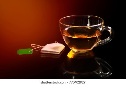Tea in a transparent glass cup and tea bag on a dark background