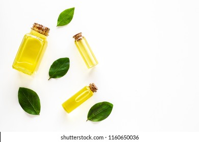 Tea tree essential oil near tea tree leaves on white background top view copy space
