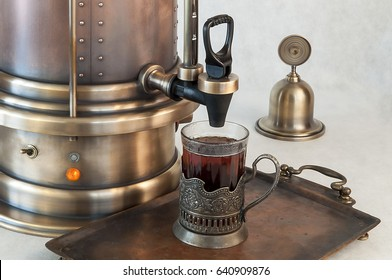 Tea urn in vintage style with glass of tea and copper tray