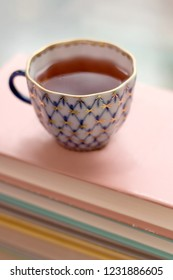 Tea in a vintage cup on stack of books. Selective focus.