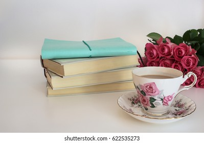 Tea in a vintage cup and saucer, pink roses and stack of books and journal