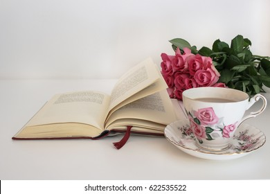 Tea in a vintage cup and saucer, pink roses and open hardback book