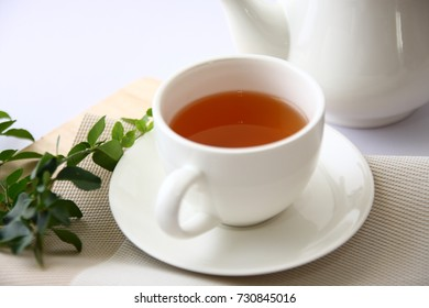 Tea in a white glass with leaves.