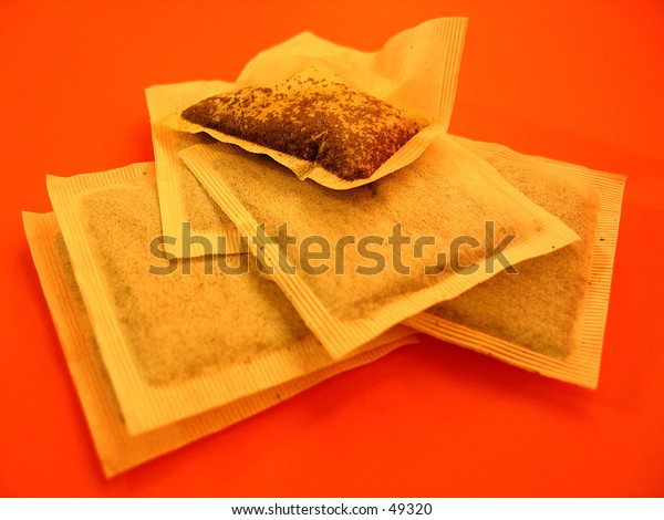 Teabags on a bright red background. Focused on  wet teabag.