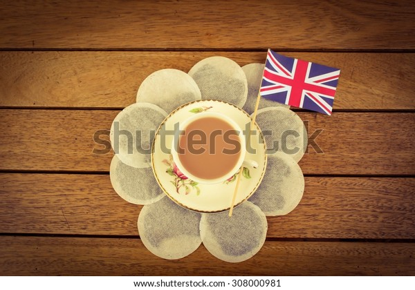Teabags surrounding a cup of tea with a union jack flag on a wooden table top