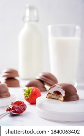 Teacakes of soft melting marshmallow centre, strawberry jam filling and chocolate coated with milk at the background