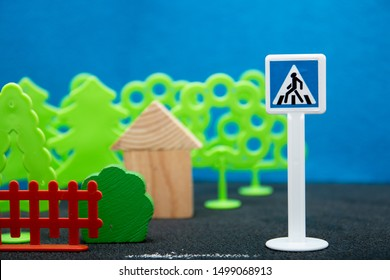 teach children the rules of behavior on the road, traffic rules, game, toy figures, trees, road sign, drawn crosswalk, zebra, house, blurred background, traffic laws
