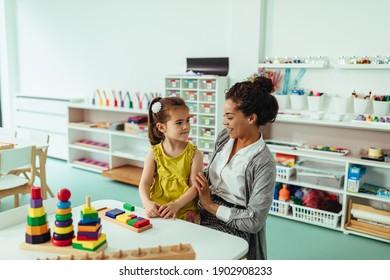 Teacher and adorable little girl playing at kindergarten