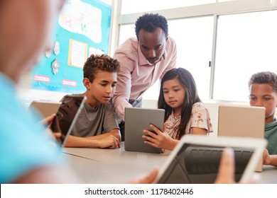 Teacher among school kids using computers in class