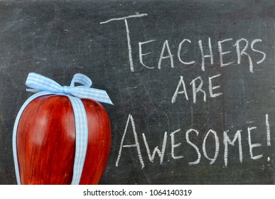 Teacher appreciation image of a red apple tied up with a cute blue ribbon in front of a worn blackboard with a message written in white chalk