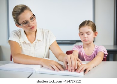 Teacher assisting blind student in library at school
