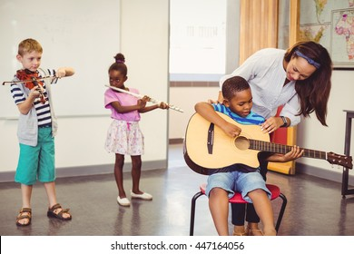 Teacher assisting a kids to play a musical instrument in classroom at school