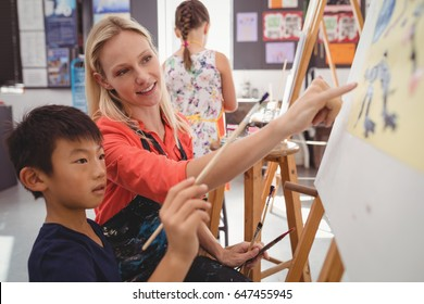 Teacher assisting schoolboy in drawing class at school