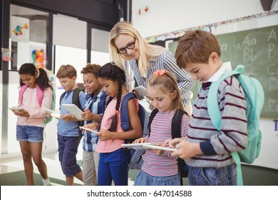 Teacher assisting schoolkids on digital tablet in classroom at school