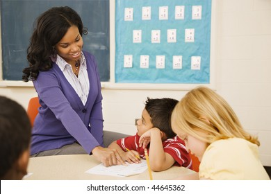 Teacher assisting young male student with lesson as he listens intently.