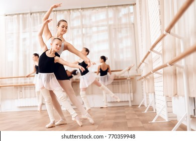 Teacher of the ballet school helps young ballerinas perform different choreographic exercises. They rehearse in the ballet class. The teacher communicates with the children.