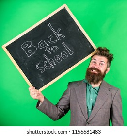 Teacher bearded man holds blackboard with inscription back to school green background. Keep working. Teaching stressful occupation. Teacher with tousled hair stressful about school year beginning.