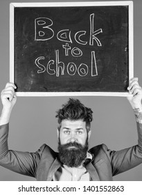 Teacher bearded man holds blackboard with inscription back to school blue background. Teacher with tousled hair stressful about school year beginning. Teaching stressful occupation. Do not be upset.
