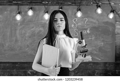 Teacher of biology holds book and microscope. Lady in formal wear on calm face in classroom. Lady scientist holds book and microscope, chalkboard on background, copy space. Biology concept.